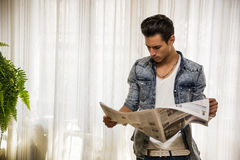 Handsome young man at home reading newspaper Royalty Free Stock Images
