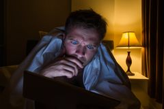 Handsome young man at home reading with tablet PC lying on bed at night. He is tired and want to sleep. But has problems on work or insomnia royalty free stock images