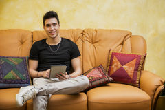 Handsome young man at home smiling, using tablet PC Stock Photos