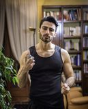 Handsome young man at home spraying cologne. Handsome muscular young man in his home spraying cologne or perfume on neck Royalty Free Stock Photos