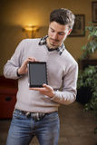 Handsome young man at home with tablet PC in his hands. Handsome young man at home in his living room showing tablet PC's screen Royalty Free Stock Photo