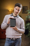 Handsome young man at home with tablet PC in his hands. Handsome young man at home in his living room showing tablet PC's screen Stock Image