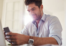 Handsome young man at home using mobile phone Royalty Free Stock Photography