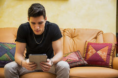 Handsome young man at home, using tablet PC Stock Image