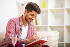 Handsome young man at home writing on notebook, sitting Stock Image