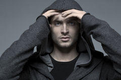 Handsome young man in a hood, hands up. Handsome young man in a hood, blue eyes Royalty Free Stock Photography