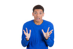 Handsome young man horrified, with eyes and mouth wide open, hands in the air Royalty Free Stock Photos
