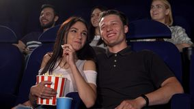 Happy couple laughing while watching comedy movie at the cinema. Handsome young men hugging his beautiful girlfriend while watching a movie together at the stock image