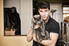 Handsome Young Man Hugging his Gray Cat Pet. Handsome Young Animal-Lover Man Inside the House, Hugging his Gray Domestic Cat Pet Stock Photo