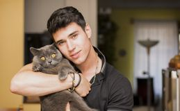 Handsome Young Man Hugging his Gray Cat Pet. Handsome Young Animal-Lover Man Inside the House, Hugging his Gray Domestic Cat Pet Stock Images
