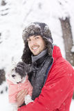 Handsome young man hugging his small white dog in the winter.Snowing Royalty Free Stock Photos