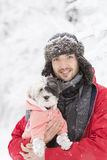 Handsome young man hugging his small white dog in the winter.Snowing Stock Photography