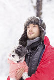 Handsome young man hugging his small white dog in the winter.Snowing Stock Photo