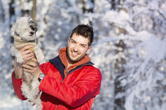 Handsome young man hugging his small white dog in the winter.Snowing Royalty Free Stock Images