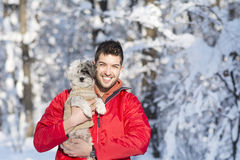 Handsome young man hugging his small white dog in the winter.Snowing Stock Images