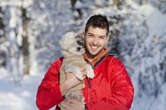 Handsome young man hugging his small white dog in the winter.Snowing Royalty Free Stock Image