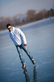 Handsome young man ice skating outdoors on a pond Royalty Free Stock Photography