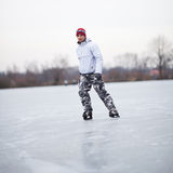 Handsome young man ice skating outdoors on a pond Royalty Free Stock Photo
