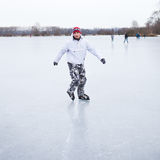 Handsome young man ice skating outdoors on a pond Royalty Free Stock Photos