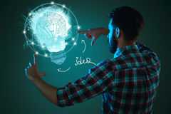 Handsome young man with idea bulb on blue Royalty Free Stock Photo