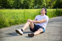 Handsome young man injured while running and Stock Image