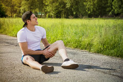 Handsome young man injured while running and Royalty Free Stock Photography