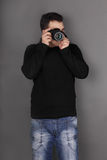 Handsome young man in jeans with modern camera shoots Stock Photo