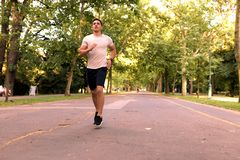 A handsome young man jogging in a park stock image