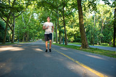A handsome young man jogging in a park Royalty Free Stock Photography