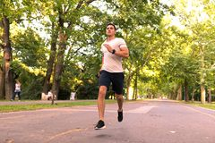 A handsome young man jogging in a park royalty free stock photo