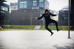 Handsome young man jumping for joy. Handsome young man in winter fashion jumping for joy midair on an outdoor urban court surrounded by buildings Royalty Free Stock Image