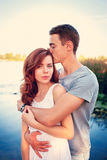 Handsome young man kissing his girlfriend. Handsome young men kissing his girlfriend near the river Stock Photos
