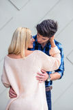 Handsome young man almost kissing a sexy blonde woman on  backgr. Handsome young men almost kissing a sexy blonde women on  a wall background Stock Image