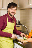 Handsome young man in the kitchen with apron cutting vegetables Royalty Free Stock Images