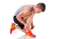 Handsome young man kneeling and tying sneaker Royalty Free Stock Photos