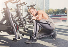 Handsome young man lace shoes at gym after training Stock Images