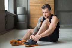 Handsome young man lace shoes at gym after training. Little break. Handsome young man in sportswear relax after training in gym, sit on floor, lacing sneakers Stock Images