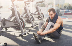 Handsome young man lace shoes at gym after training Royalty Free Stock Image