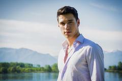 Handsome young man on a lake in a sunny, peaceful Stock Photography