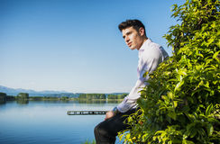 Handsome young man on a lake in a sunny, peaceful Stock Images