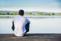 Handsome young man on a lake in a sunny, peaceful. Day, sitting on a wood pier, thinking or meditating Stock Photo