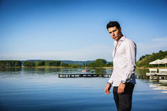 Handsome young man on lake in a sunny, peaceful Royalty Free Stock Photo