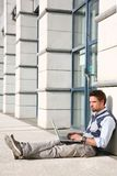 Handsome young man with laptop. Sitting and thinking royalty free stock photography