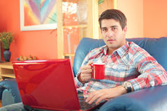 Handsome young man with laptop and coffee cup Stock Photography