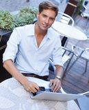 Handsome young man with laptop Stock Image
