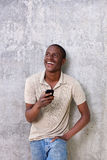 Handsome young man laughing with mobile phone. Portrait of handsome young man laughing with mobile phone Royalty Free Stock Photos