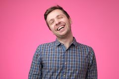 Handsome young man laughing on pink background stock image