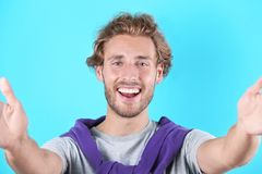Handsome young man laughing and taking selfie. On color background stock photography