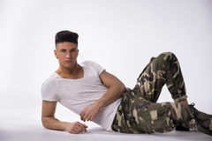 Handsome young man laying down on floor, white background Royalty Free Stock Photography
