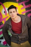 Handsome young man leaning against graffitti wall Stock Images